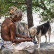 Indian people and dog sits on the ghat along the Ganges river. Rishikesh, India — Stock Photo #70988993