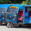 Auto rickshaw taxis on a road. These iconic taxis have recently been fitted with CNG powered engines in an effort to reduce pollution — Stock Photo #70990731