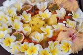 Fruit dessert salad with pineapple, papaya, passion fruit, and white frangipani flower  — Stock Photo