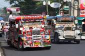 Jeepneys passing, Filipino inexpensive bus service.  — Stock Photo