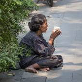 Thai old beggar woman waits for alms on a street   — Stock Photo