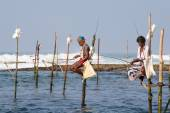 Unidentified local fishermen are fishing in unique style. This type of fishing is traditional for South Sri Lanka in Indian ocean. — Stock Photo