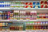 Selection of yogurts, soy milk and milk on the shelves in a supermarket Siam Paragon in Bangkok, Thailand. — Stock Photo