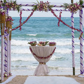 Wedding arch decorated with flowers on tropical sand beach, outdoor beach wedding setup — Stock Photo