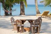 Empty wooden table and chairs of a beach tropical garden near the sea — Stock Photo