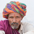 Indian man, sits on the ghat along the sacred Sarovar lake in Pushkar — Stock Photo #73041043