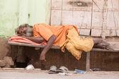 Indian homeless man sleeps  near the ghat along the sacred Sarovar lake — Stock Photo