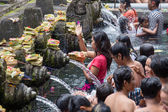 Balinese families come to the sacred springs water temple of Tirta Empul in Bali, Indonesia to pray and cleanse their soul — Stock Photo