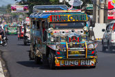 Jeepneys passing, Filipino inexpensive bus service. Philippines. — Stock Photo