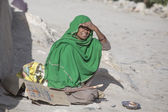 Poor woman begs for money from a passerby in Leh.  India — Stock Photo