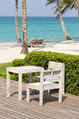 Beautiful sea, coconut palm tree, wooden table and chairs — Stock Photo