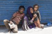 Indian poor woman with children begs for money from a passerby on the street in Srinagar, India — Stock Photo