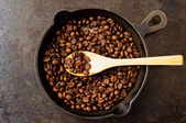 Spoon roasting coffee beans in a pan — Stock Photo