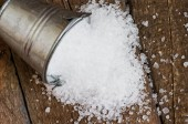 Salt is scattered on the wooden table — Stock Photo