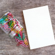 Open blank notebook with paper clips over a wooden background. — Stock Photo #55941071