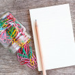 Open blank notebook with paper clips over a wooden background. — Stock Photo #55941179