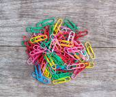 Colorful paperclips on wood background — Stock Photo