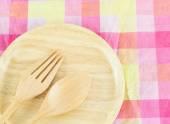 Cuchara de madera y horquilla en chapa de madera sobre un mantel — Foto de Stock