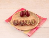 Red grapes in wooden plate on a wooden table background — Stock Photo