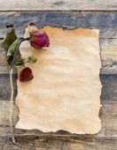 Old paper with dried rose on wooden — Stockfoto