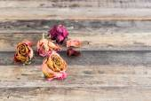 Beautiful dried roses on wooden background — Stock Photo