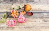 Dry rose and the condom on wooden background — Stock Photo