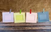Paper photo frame on clothesline on grunge background — Stock Photo