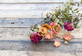 Dry rose on wooden background — Stock Photo