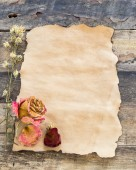 Old-paper with dried rose on a wooden background — Foto de Stock