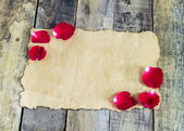Fresh red rose and old paper on wooden background — Stock Photo