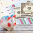 Piggy bank on wooden table over dollars and financial paper grap — Stockfoto #69968481