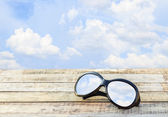Clear sky in eyeglasses on the wooden background — Stock Photo