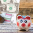 Piggy bank on wooden table over blurred smart phone and dollars — Stock Photo #70846601