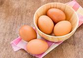 Huevos en un cuenco de madera sobre la mesa — Foto de Stock