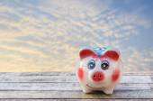 Piggy bank on wooden table over blurred sky background. — Stock Photo