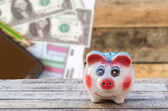 Piggy bank on wooden table over blurred smart phone and dollars — Stock Photo