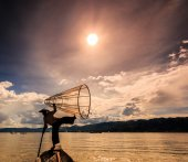 рыбак на лодке ловить рыбу от традиционных net — Стоковое фото