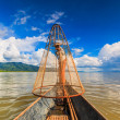 Fisherman on boat catching fish by traditional net — Stock Photo #54900953