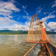 Fisherman on boat catching fish by traditional net — Stock Photo #54901039