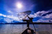 Fisherman on boat catching fish by traditional net — Stock Photo