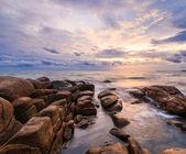 Sunset over rocks beach — Stock Photo
