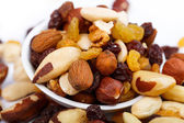 Mixed nuts and sultanas on a plate on a white background — Stock Photo