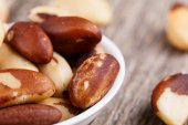 Brazil nuts on a plate on wooden background. — Stock Photo
