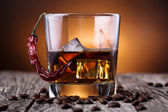 Glass of whiskey with ice and wheat on a wooden table. — Stock Photo