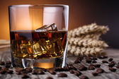 Glass of whiskey with ice and wheat on a wooden table. — Foto de Stock