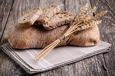Tasty bread with wheat on wooden background. — Stock Photo