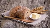 Вкусный хлеб с пшеницей на деревянных фоне. — Стоковое фото
