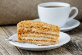 Tasty honey cake with cup of coffee on wooden background. — Stock Photo