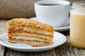 Tasty honey cake with jar of honey. — Stock Photo