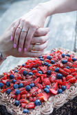 Couple hands with wedding ring and chocolate cake with berries. — Stock Photo